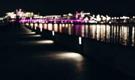 Abstrakt bakgrund av suddiga stadsljus med reflekterad bokeheffekt p? vatten royaltyfri fotografi