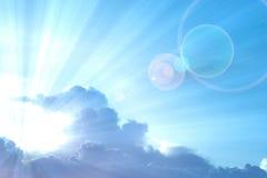 Abstrakt bakgrund: Blå himmel med solstråle som sticker fram från molnet Arkivbild