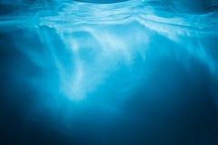Abstrakt bakgrund för blått vatten med solstrålar royaltyfria foton