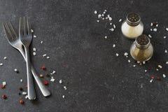 Abstrakt bakgrund för grå färger med salta och pepparshaker för gafflar, placera text Royaltyfri Foto