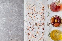 Abstrakt bakgrund för grå färger med utrymme för text Olivoljakrus, vinrankavinägerkrus, bunke med oliv på en vit torkduk med Arkivfoto