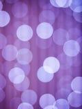 Abstrakt bakgrund för lilor med defocused ljus för bokeh Royaltyfri Bild