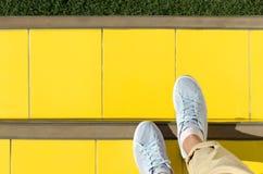 Abstrakt bakgrund - foots i ljus - blåa gymnastikskor är på trappa som täckas med gula tegelplattor, framåt grön gräsmatta Royaltyfri Bild