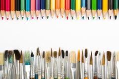 Abstrakt bakgrund från färgblyertspennor och målarpenslar Arkivfoto