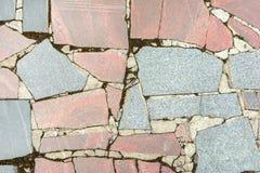 Abstrakt bakgrund med en textur av en stenmosaik Stora grå färger och bleka röda granitfragment fodras kaotiskt Royaltyfri Fotografi