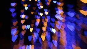 Abstrakt bakgrund med kulöra ljus i formen av hjärtor arkivfilmer