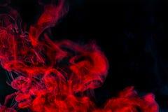Abstrakt bakgrund, röd röktextur i luften Rökfragment som isoleras på mörk bakgrund Royaltyfria Foton