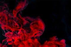 Abstrakt bakgrund, röd röktextur i luften Rökfragment som isoleras på mörk bakgrund Arkivbild