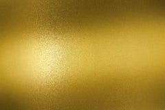 Abstrakt bakgrund, refraktion på den guld- metalliska väggen i mörkt rum royaltyfri fotografi
