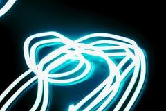 Abstrakt bakgrund som skapas av rörelsen av en blå stråle av ljus, foto arkivbild