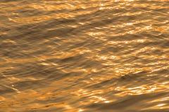 Abstrakt bakgrund, textur av krusningar i en flod, i golden Royaltyfri Fotografi