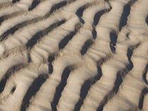 Abstrakt bakgrundstextur av sand med ridged krusningar bildade vid handlingen av vattnet i en full rammodell för flotta eller va Royaltyfri Bild