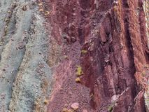 Abstrakt bakgrundstextur av sandstenen vaggar ljust rött, burgundy och gräsplan Arkivbild