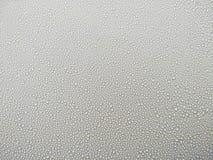 Abstrakt bakgrundsvatten tappar på exponeringsglas, regndroppar på fönsterexponeringsglas Arkivfoto