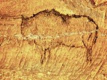 Abstrakt barnkonst i sandstengrotta. Svart kolmålarfärg av bisonen på sandstenväggen royaltyfria bilder
