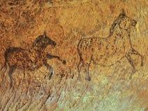 Abstrakt barnkonst i sandstengrotta. Svart kolmålarfärg av hästar Royaltyfri Fotografi