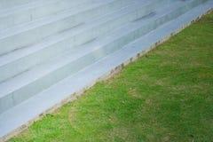 Abstrakt begrepp av arkitekturbetongtrappuppgången bredvid ängfält för grönt gräs på utomhus- Royaltyfri Foto