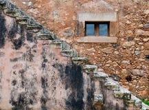 Abstrakt begrepp av en brun stenvägg med fönstret och trappa Arkivfoton