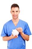 Abstrakt begrepp för doktor Holding Piggy Bank Arkivbild