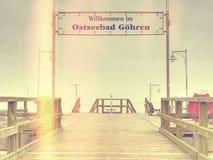 Abstrakt begrepp Gammal wood strandbro i Goehren med inget Höstlig mist royaltyfri fotografi