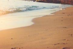 Abstrakt begrepp - havs- och strandsand på solnedgång Arkivfoton