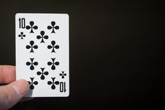 Abstrakt begrepp: man handinnehavet som spelar kort tio av klubbor som isoleras på svart bakgrund med copyspace arkivbilder