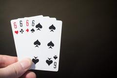 Abstrakt begrepp: manhandinnehavet som spelar kortet fyra sex, isolerade på svart bakgrund med copyspacepokeruppsättningen fyra s Arkivfoton