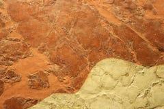 Abstrakt begrepp- och grungebakgrund i beige och rostigt orange - extrem closeup av brutet och reparerat dekorativt område av gam royaltyfri bild
