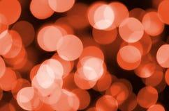 Abstrakt begrepp som är suddigt av röd blänka bakgrund för skenkulaljus Suddighet av begreppet för jultapetgarneringar royaltyfri foto
