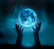 Abstrakt begrepphänder, medan be på den blåa fullmånen med stjärnan i mörk bakgrund för natthimmel Royaltyfri Fotografi