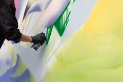 Abstrakt begreppsgrafittigata Art Culture Spray Konstnären målar en bild på väggen Vandalism eller konst arkivfoton