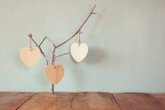 Abstrakt bild av att hänga trähjärtor över träbakgrund arkivfoto