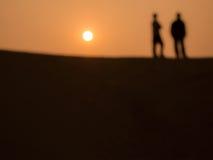 Abstrakt bild av 2 män på öknen i solnedgångtid Royaltyfria Foton