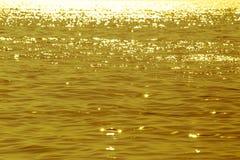 Abstrakt bild av yttersidavatten av havet eller havet på solnedgångtid med guld- ljus Royaltyfri Bild