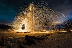 Abstrakt bild med banor av brinnande gnistor nära trädet på bakgrunden av nattlandskapet Arkivbilder