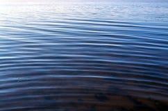 Abstrakt blå bakgrund av vattenyttersida på med vågor Royaltyfri Foto