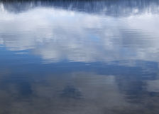 Abstrakt blå himmel och moln reflekterade i sjövatten Fotografering för Bildbyråer