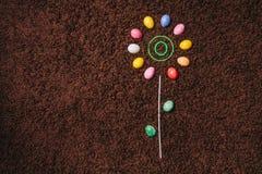 Abstrakt blomma med kulöra ägg på mattan Påsk plan la Arkivfoto