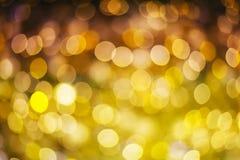 Abstrakt bokeh för guld och för lilor eller defocused bakgrundsglitterin Royaltyfria Foton
