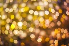 Abstrakt bokeh för guld och för lilor eller defocused bakgrundsglitterin Arkivfoton