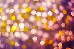 Abstrakt bokeh för guld och för lilor eller defocused bakgrundsglitterin Fotografering för Bildbyråer