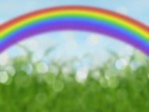 Abstrakt bokehregnbågebakgrund med blå himmel och gräs Royaltyfria Bilder