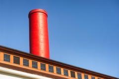 Abstrakt czerwona dymna sterta przeciw niebieskiemu niebu Zdjęcia Stock