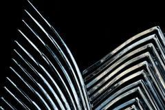 Abstrakt designbakgrund, ljusa skinande metalliska sicksackar på en svart bakgrund Arkivbilder