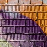 Abstrakt detalj av tegelstenväggen med fragmentet av violetta och orange grafitti Stads- konstnärbild, för bakgrundsbruk Royaltyfri Bild