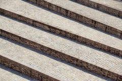 Abstrakt diagonal trappa, gammal sliten granittrappuppgång på en stadsfyrkant, brett stentrappaperspektiv som ofta nära ses Royaltyfri Bild