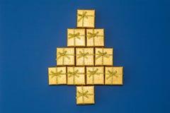 Abstrakt diagram av en julgran av gåvaaskar Guld- julgåvor på blå bakgrund Arkivbild