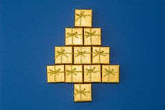 Abstrakt diagram av en julgran av gåvaaskar Guld- Kristus Arkivfoto