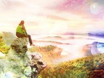 abstrakt effekt Turisten sitter på maximum av sandsten vaggar och hålla ögonen på in i färgrik mist och dimma i morgondalen Fotografering för Bildbyråer