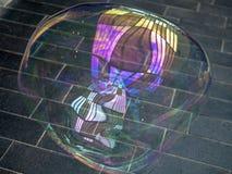 Abstrakt färgreflexion i en stor ljus såpbubbla på bakgrunden av pavers Royaltyfri Fotografi